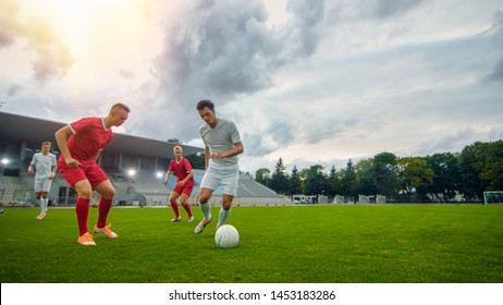 Professional Soccer Player Leads with a Ball, Masterfully Dribbling and Bypassing Sliding Tackles of His Opponents. Two Professional Football Teams Playing. Low Angle Shot. Warm Sunlight Flare.