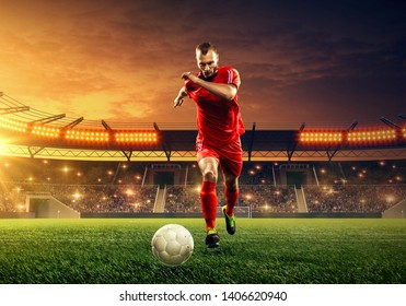 Professional soccer player in red uniform ready to kick a ball. Action. Floodlit soccer stadium
