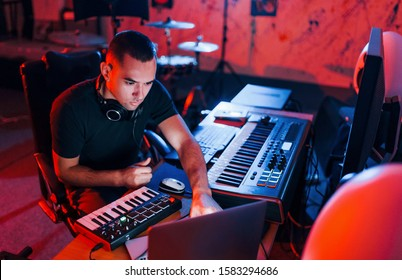 Professional sound engineer working and mixing music indoors in the studio.