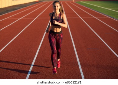 Professional sportswoman athlete sprinter running on stadium track in evening. Healthy lifestyle concept. Forward to the victory.