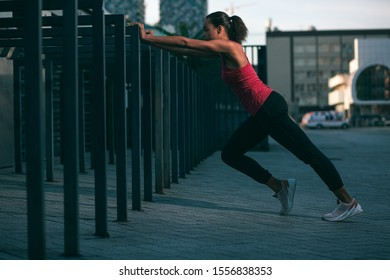 Professional sportswoman putting hands on the banister and doing push ups