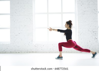 Professional sportswoman spending free time on active lifestyle doing exercise for butt muscles in modern white interior on copy space area for your advertising, attractive slim girl practicing in gym