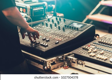 professional stage sound mixer closeup at sound engineer hand using audio mix slider working during concert performance - Shutterstock ID 1027504378
