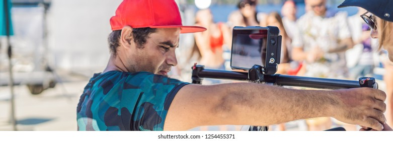 Professional steadicam operator uses a 3-axis camera stabilizer system on a commercial production set BANNER, LONG FORMAT