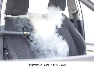 Professional steam cleaning of automobile interior front seats without chemicals. Car wash and sanitization process concept.
