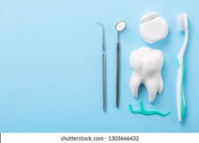 Professional steel dental instrument with a mirror near white tooth model, toothbrush and dental floss on light blue background with free space. Dental health and teethcare concept.