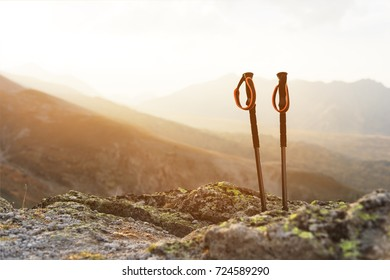 Professional sticks for climbing a mountain near a stone on a high mountain path against a blue sky and white clouds on sunset
