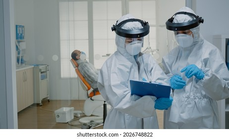 Professional stomatologists wearing ppe suits at oral clinic discussing dental operation for patient sitting in cabinet. Dentists preparing for consultation during coronavirus pandemic
