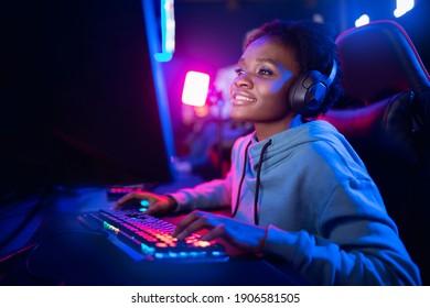Professioneller Streamer afrikanische junge Frau Cyber-Gamer-Studio-Raum mit PC-Sessel, Tastatur auf neonfarbigem unscharfem Hintergrund.