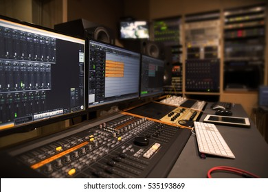 Professional studio control room with lot of studio equipment in the background.