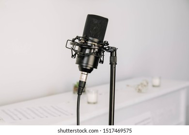 Professional studio microphone on a modern tripod, very convenient and practical. White background