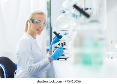 Professional study. Delighted nice female biologist sitting in front of the microscope and smiling while doing her job