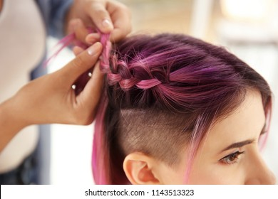 Professional stylist braiding woman's color hair in beauty salon. Modern trend