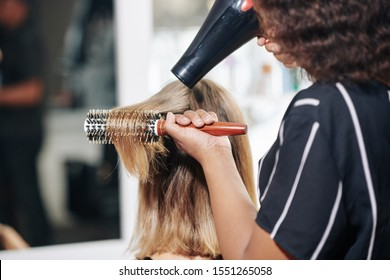 Professional stylist brushing and blowdrying hair of female client, view from the back