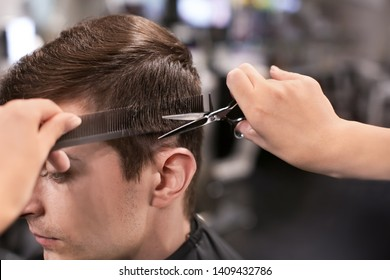 Professional stylist cutting client's hair in salon, closeup