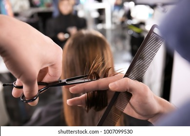 Professional stylist cutting woman's hair in salon, closeup