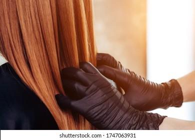 Professional stylist évalue les cheveux après la kératine de la procédure. botox