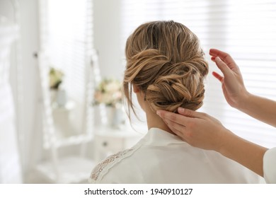 Professional stylist making wedding hairstyle for bride in salon, back view