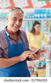 Professional supermarket clerk using a touch screen tablet and working, he is smiling at camera