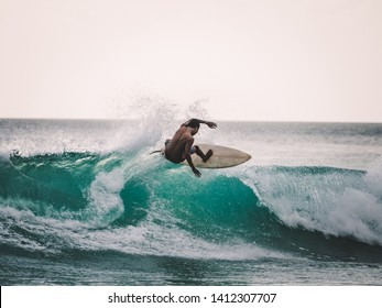 professional surfer riding waves in Bali, Indonesia. men catching waves in ocean, isolated. Surfing water board sport