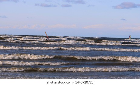 Professional surfer in the wind preparing the wind in the sea to the ocean. Windsurfer catches the wave in a storm. Concept of: Sport, Lifestyle, Board, Waves, Slow Motion
