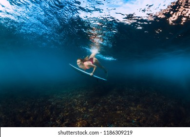 Professional surfer woman with surfboard dive underwater with under wave.