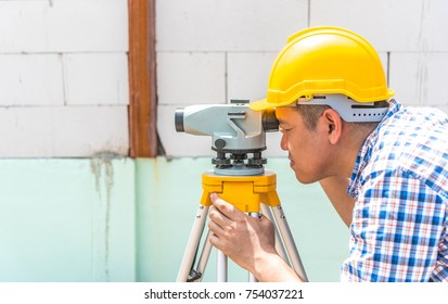 Professional surveyor engineer or architect working and measuring level at construction site for renovate improve and develop factory space, close up camera