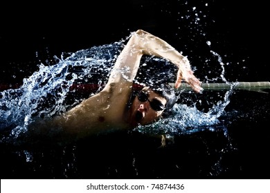 Professional swimmer crawl freestyle isolated black background