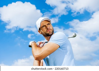 Professional swing. Low angle view of young and confident golfer swinging his driver and looking away with blue sky as background
