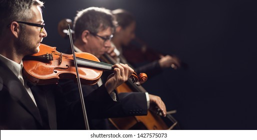 Professional symphonic orchestra performing on stage and playing a classical music concert, violinist playing in the foreground, arts and entertainment concept - Shutterstock ID 1427575073
