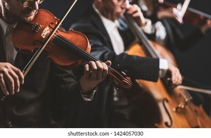 Professional symphonic string orchestra performing on stage and playing a classical music concert, violinist in the foreground