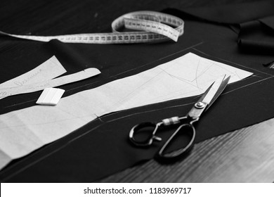 Professional tailor tools set - paper templets, choke, measure tape and scissors on marked fabric. Tailor atelier - handmade exclusive clothes making and repair, creative occupation concept