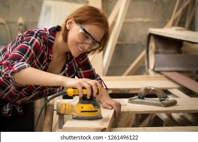 Professional and talented craftswoman smiling and working with electric sender and lumber in carpentry shop. Beautiful and positive woman wearing checked shirt and safety glasses.