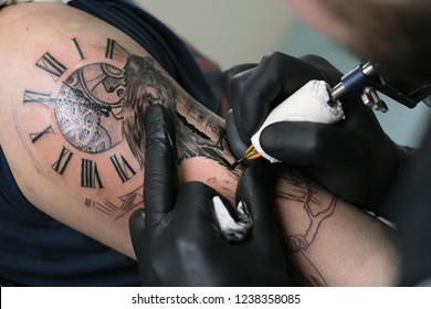 A professional tattoo artist introduces black ink into the skin using a needle from a tattoo machine. tattoo art on body..Professional tattooist working tattooing in studio. Selective focus