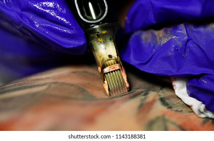 A professional tattoo artist introduces ink into the skin using a needle from a tattoo machine. tattoo art on body.Makes a tattoo.Professional tattooist working tattooing in studio. Selective focus