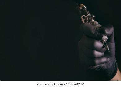 Professional tattoo artist with machine on black background