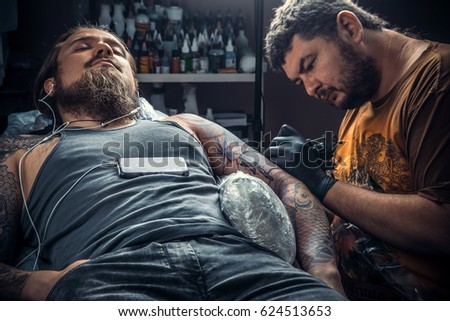 0d08d0735 Professional tattoo artist posing in studio./Master makes tattoo pictures  in tattoo studio.