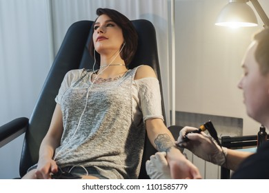 Professional tattooer doing picture on client hand by machine while girl listening music. Tattoo art on body. Popular body modification, modern lifestyle, copy space