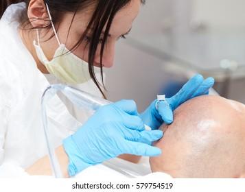 professional tattooist making permanent make up tricopigmentation