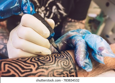 A professional tattooist is tattooing a tribal design on the left forearm of a costumer.