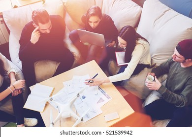 Professional team brainstorming sitting at the table of coworking space, reading reports accounting numbers of company clients while discussing ideas and concepts for successful business plan