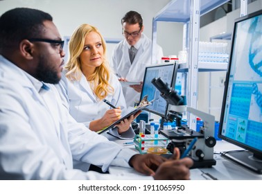 Professional team of scientists is working on a vaccine in a modern scientific research laboratory. Genetic engineer workplace. Future technology and science.