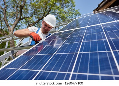 Professional technician attaching solar photo voltaic panel to high metal platform. Exterior solar system installation, cheap green ecological energy production concept.