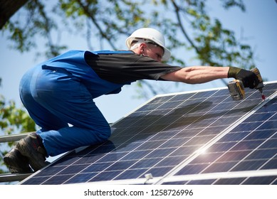Professional technician connecting shiny solar photo voltaic panel to metal platform using screwdriver. Exterior solar system installation, renewable green energy generation concept.