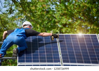 Professional technician connecting solar panel to metal platform using screwdriver. Exterior solar system installation, renewable green energy generation concept.