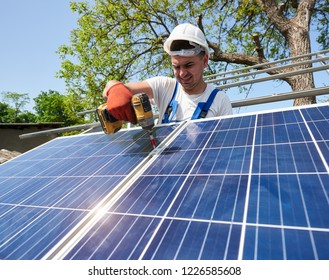 Professional technician installing shiny solar photo voltaic panel to metal platform using screwdriver. Exterior solar system installation, renewable green energy generation concept.