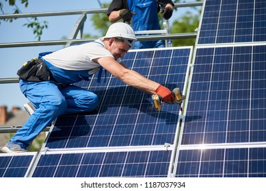 Professional technician installing solar panel to metal platform using screwdriver. Exterior solar system installation, renewable green energy generation concept.