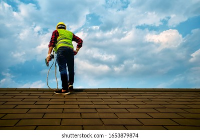Professional technician Roof repair  Standing action on the roof top Hold the drive screw tool in hand - Shutterstock ID 1653879874