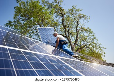 Professional technicians connecting solar photo voltaic panel to metal platform using screwdriver on bright blue sky and green tree background. Stand-alone exterior solar panel system installation.