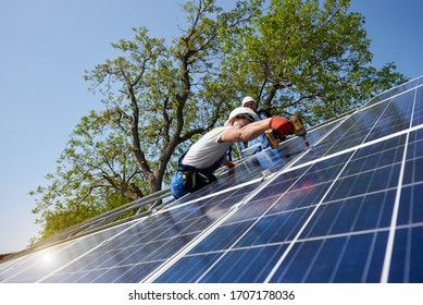 Professional technicians installing solar photo voltaic panel to metal platform using screwdriver on bright blue sky and green tree background. Stand-alone exterior solar panel system installation.